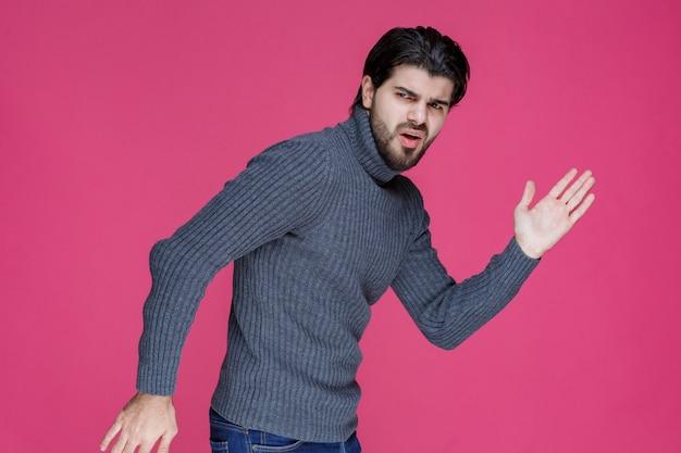 Man in grijze trui die van de scène wegrent.