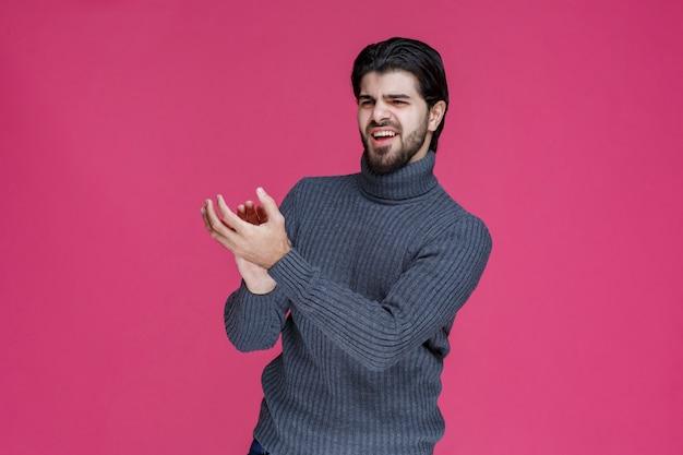Man in grijze trui iemand met veel energie en enthousiasme introduceren of begroeten.