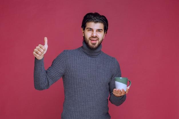 Man in grijze trui met een koffiemok en genietend van de smaak.