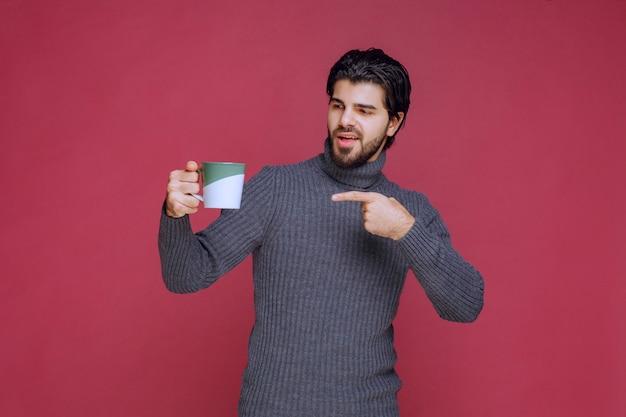 Man in grijze trui met een koffiemok en wijst erop.