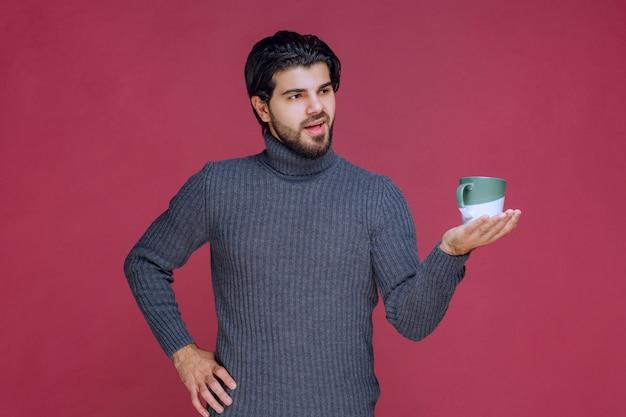 Man in grijze trui met een koffiemok in de hand.