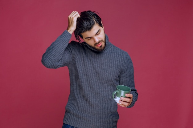 Man in grijze trui met een mok en denken.
