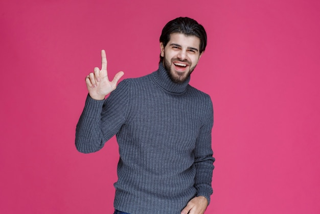 Man in grijze trui om iets te wijzen of iemand te introduceren die wijsvinger gebruikt.
