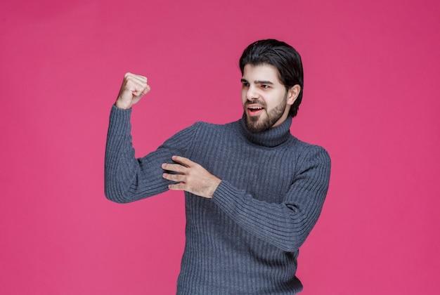 Man in grijze trui zijn armspieren demonstreren.