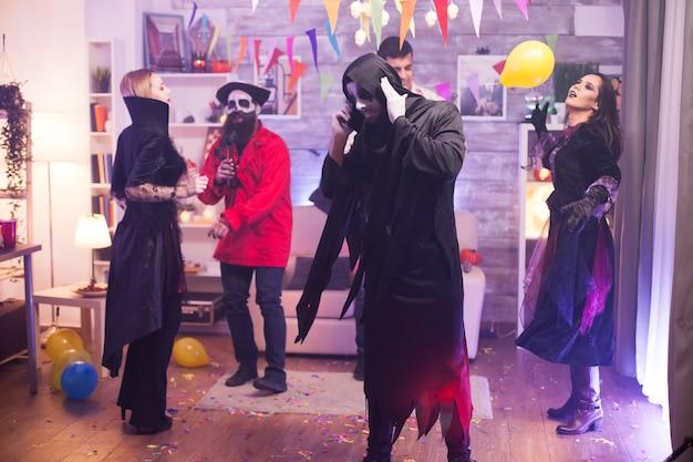 Man in grim reaper-kostuum kan niet praten aan de telefoon terwijl hij halloween viert met zijn vrienden.