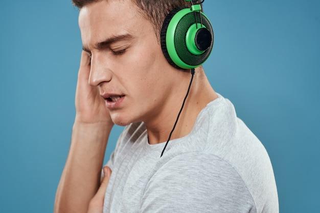 Man in groene koptelefoon luistert naar muziek entertainment levensstijl wit t-shirt