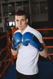 Man in handschoenen. bokser in een sportkleren. kerel in een t-shirt.