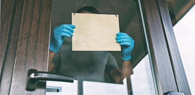Man in handschoenen en medisch masker houdt leeg houten bord bij ingang in café