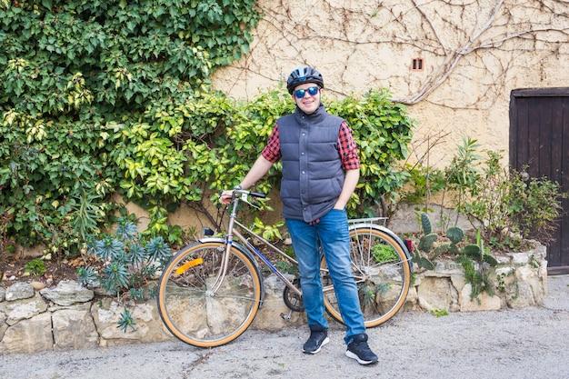 Man in helm en bril blijft op de fiets in de tuin