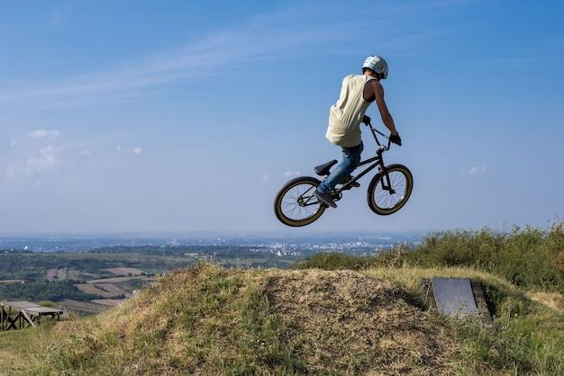 Man in helm op een fiets springen en vliegen op een heuvel tegen de blauwe hemel