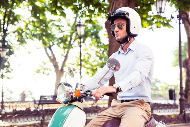Man in helm rijden op scooter