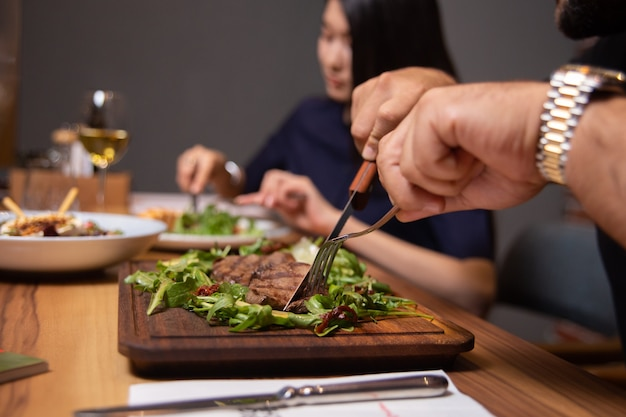 Man in het café eet biefstuk met groenen close-up.