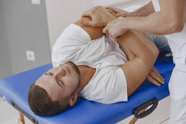 Man in het medische kantoor. fysiotherapeut is weer aan het revalideren.