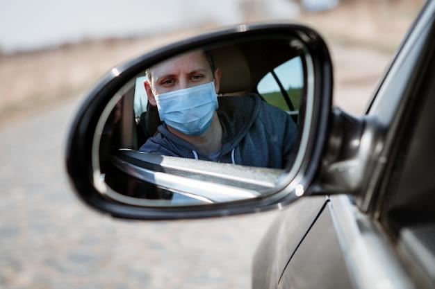 Man in het medische masker in de auto. coronavirus, ziekte, infectie, quarantaine, covid-19