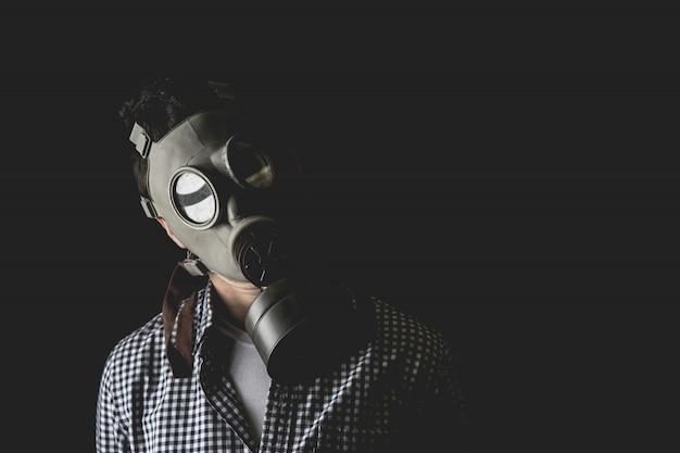 Man in het oude militaire gasmasker, ontsnapt aan de realiteit van de taken van het leidinggevende leven.