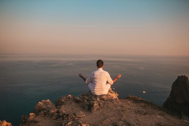 Man in het wit buiten op de rand van de klif geniet van het uitzicht en mediteert