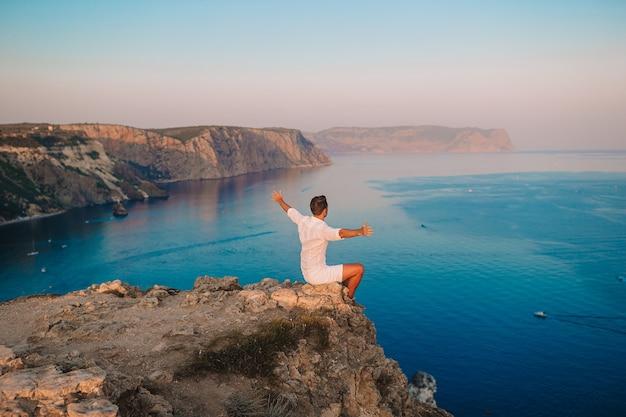 Man in het wit buiten op de rand van de klif genieten van het uitzicht