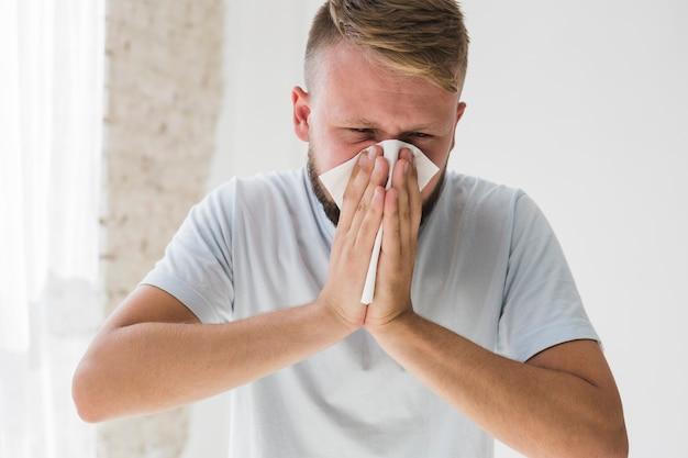 Man in het wit lijdt aan verkoudheid