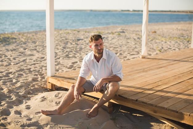 Man in het witte shirt en korte broek zittend op het strand.