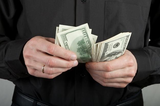 Man in het zwart telt geld dollars in handen