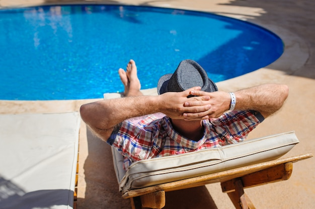 Man in hoed zonnebaden op een ligstoel bij het zwembad