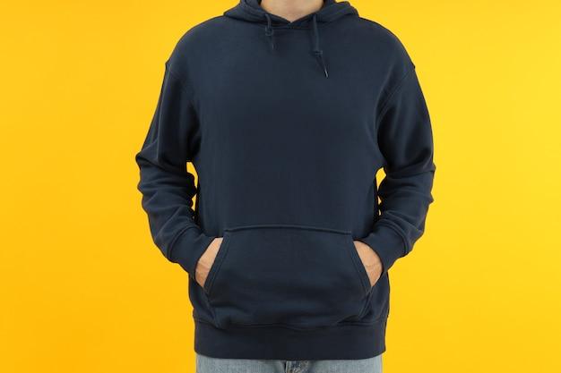 Man in hoodie met handen in zak op gele achtergrond.