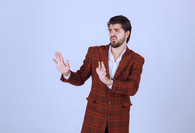 Man in ingecheckte jas die iemand met handgebaren tegenhoudt.
