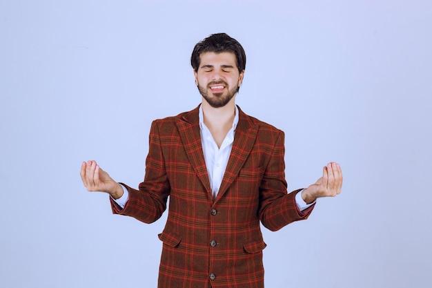 Man in ingecheckte jas die meditatie maakt.