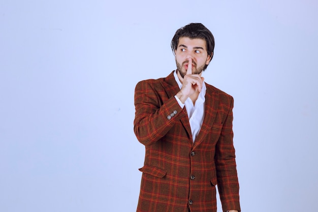 Man in ingecheckte jas die stilte vraagt door zijn mond te tonen.