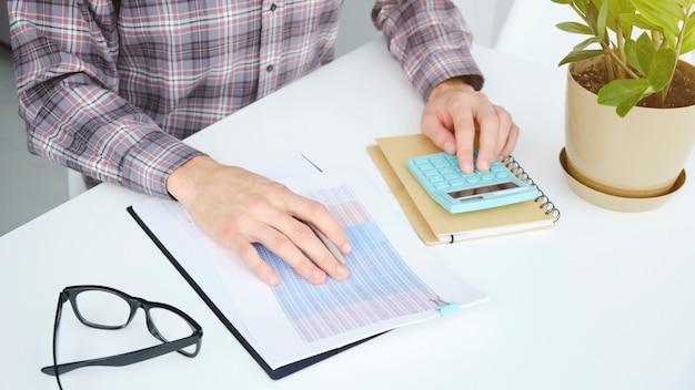 Man in kantoor achter tafel aan het werk op laptop