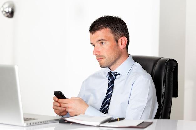 Man in kantoor met laptop die een bericht verzendt