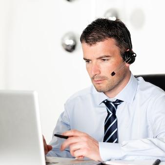 Man in kantoor met laptop en hoofdtelefoon op zijn hoofd