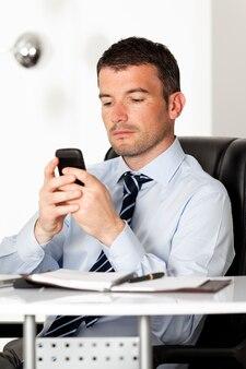 Man in kantoor met telefoon die een bericht leest