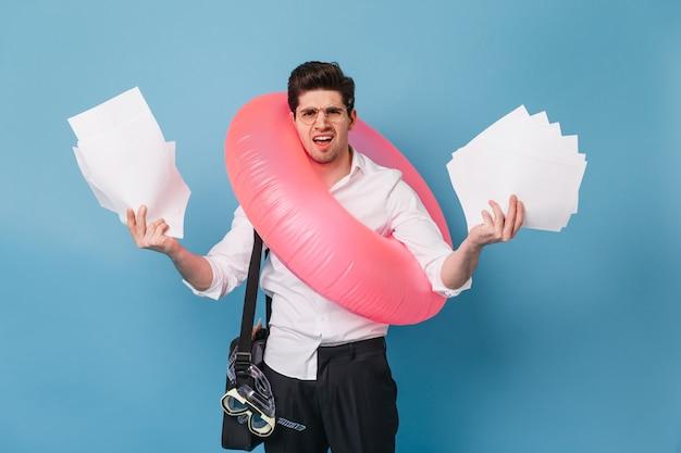 Man in kantoorkleren gooit zijn werkpapieren weg, op vakantie gaan met opblaasbare cirkel.