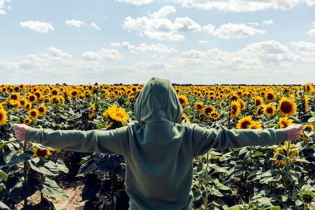 Man in kap staat in een groot veld met zonnebloemen. zomertijd. achteraanzicht. aantrekkelijke mens die zich op zonnebloemgebied bevindt.
