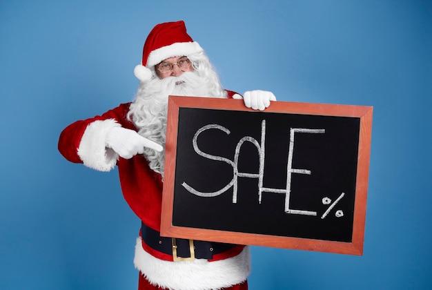 Man in kerstman kostuum met kerst banner