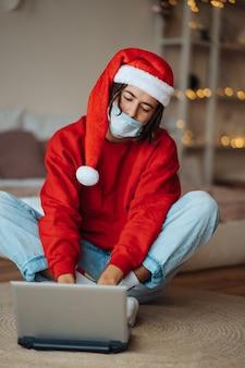 Man in kerstmuts in de buurt van de laptop werkt via videogesprekken. kerst in isolatie thuis. sociale afstand nemen voor vakanties.
