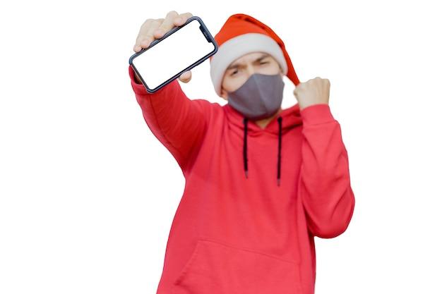 Man in kerstmuts met een mobiele telefoon en een masker als een symbool van kerstviering 2020 in pandemische tijden.