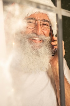 Man in kerstmuts praten op smartphone door raam