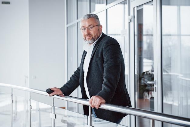 Man in klassieke kleding staat in een modern gebouw en leunde tegen de reling