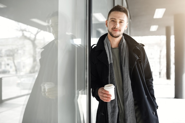 Man in koele lente kleding ontspannen terwijl buiten het drinken van koffie.