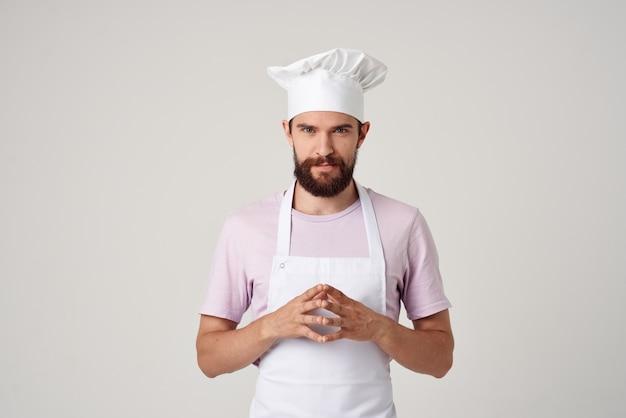 Man in kokskleding koken voedsel keuken beroep lichte achtergrond