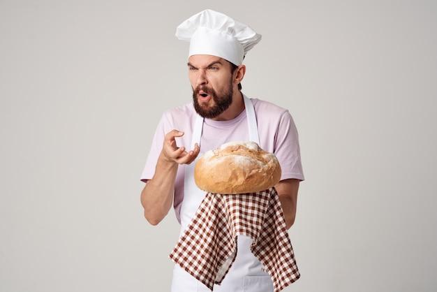 Man in koksuniform vers brood gastronomische gebakken goederen koken