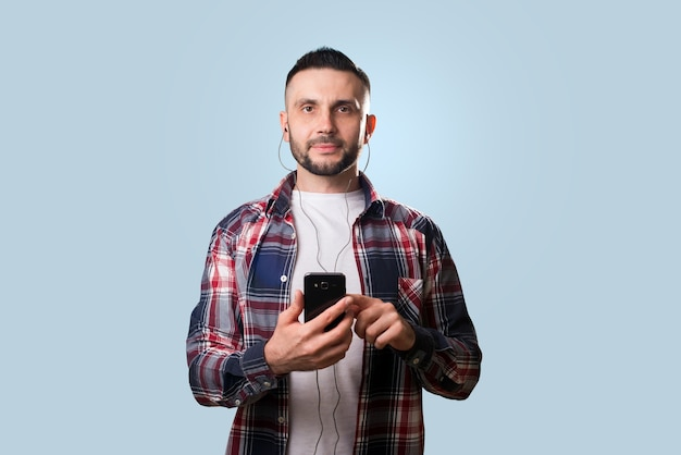 Man in koptelefoon met smartphone op blauw