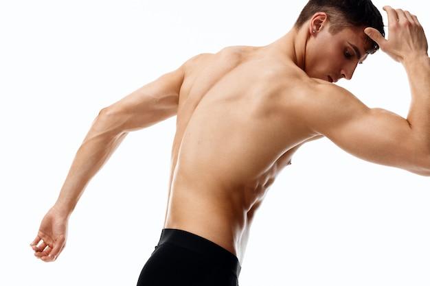 Man in korte broek en met zijn handen omhoog gebogen naar de zijkant op een lichte achtergrond bijgesneden weergave