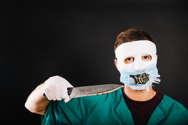 Man in kostuum dat dreigt met mes