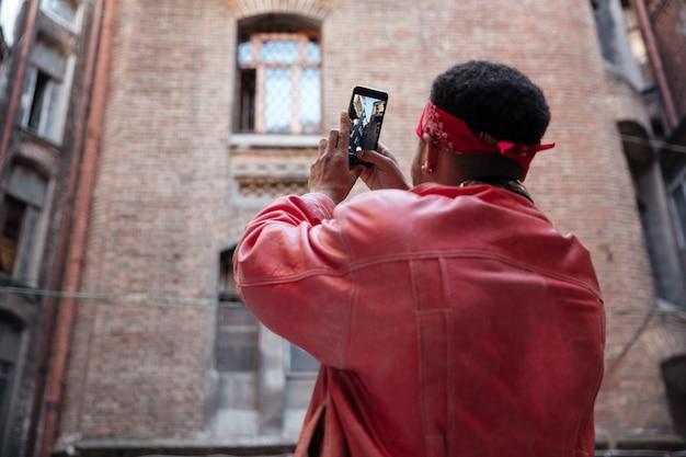 Man in lederen jas nemen foto met mobiele telefoon