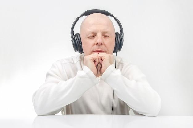 Man in lichte kleding met draagbare hoofdtelefoon op ware grootte luistert naar muziek