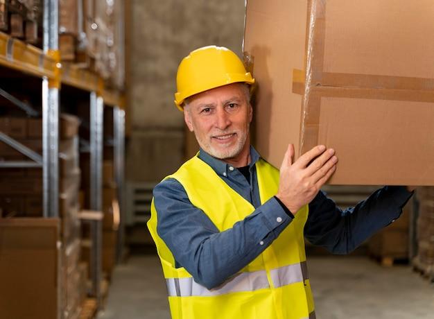 Man in magazijn met doos