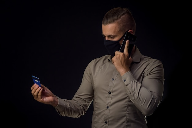Man in masker bestellingen online over zwarte muur